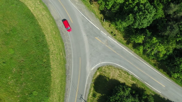Aerial view of a car driving on a road.